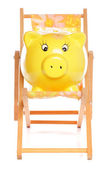 Yellow piggybank on deckchair — Stock fotografie