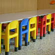 Stock Photo: Colored row of empty chairs in dining room of kindergarten