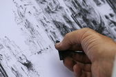 Hand of a road artist that it designs with the coal — Stock Photo