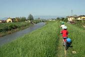 Enfants à vélo sur un petit sentier d'une berge d'une rivière au printemps — Photo