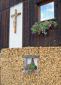 Ledge of a window surrounded by flowers freshly cut wood and wooden crucifi — Stock Photo
