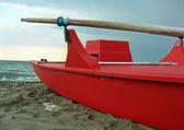 Barco de resgate vermelho com remos de madeira ao longo da praia — Foto Stock