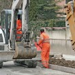 Workers with the jumpsuit and a bulldozer to work in a road construction si - Stock Photo