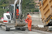 Workers with the jumpsuit and a bulldozer to work in a road construction si — Stock Photo