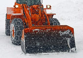 Orange snow plow clears the streets during a snow storm — Stock Photo