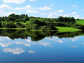Blue sky of Ireland with forests and green meadows and reflections on the c — Stock Photo