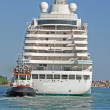 Huge cruise ship sets sail from the port of Venice accompanied by a small t — Stock Photo