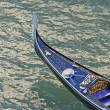Feature gondola in Venice with hat navigating the Grand Canal - Stock Photo