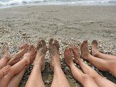 Blote voeten van een familie aan de oever van de zee — Stockfoto