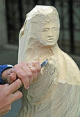 Sculptor who carves a wooden statue — Stock Photo