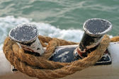 Strong brown knotted rope of the ship at berth — Stock Photo