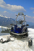 Snowmobile parked in the mountain on snowy slopes — Stock Photo