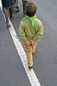 Carefree child who walks with his hands behind his back — Stock Photo