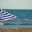 Striped umbrella on the beach and sea in the background — Stock Photo
