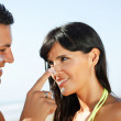 Couple on the beach putting on cream — Stock Photo #7315249
