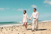 Couple walking along the beach — Stock Photo