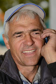 快乐,微笑着说在电话上一顶帽子的男人 — 图库照片