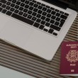 Stock Photo: Laptop, passport placed on glass tabletop.