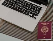 Ordenador portátil, pasaporte colocado sobre una mesa de vidrio. — Foto de Stock