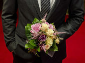 Wedding bouquet in hands of the groom — Stock Photo