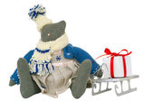 Stuffed cat toy in dress, sled with present nearby — Stock Photo