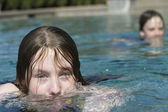 Girl blows bubbles in pool — Stock Photo