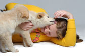 Two puppies play with girl — Stock Photo