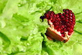 Pomegranate heart on lettuce — Stock Photo
