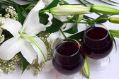 Lily bouquet and two glasses of red wine — Stock Photo