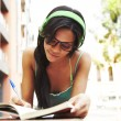 Cute girl listening music and studying — Stock Photo