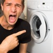 Young man unhappy with washing mashine — Stock Photo
