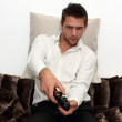 Gamer sitting on couch with controller and playing — Stock Photo