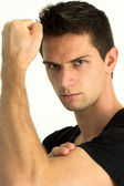 Man showing he's arm muscles and smiling — Stock Photo