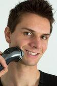 Man shaving face with electric razor — Stock Photo