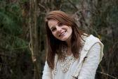 Ormanda sırasında kış gülümseyen genç kadın — Stok fotoğraf