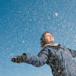 Enjoying winter - woman throwing snow — Stock Photo