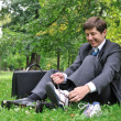 Senior business man changing shoes in park — Foto de Stock