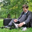 Senior business man changing shoes in park — Stockfoto