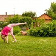 Stock Photo: Child doing cartwheel in backyard