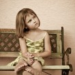 Child portrait - siting on bench - Stock Photo