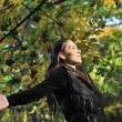 Woman enjoys sun in fall time outdoors — Stock Photo