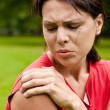 Shoulder injury - sportswoman in pain - Stock Photo