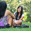 Two friends - girls talking outside in park — Stock Photo