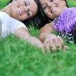 Two smiling sisters lying outdoors in grass holding hands — Stock Photo
