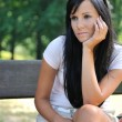 Young pensive woman siting on bench - Stock Photo