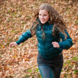 Stock Photo: Autumn pleasure - young womruning