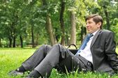 Senior business man siting in nature — Stock Photo