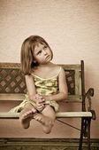 Child portrait - siting on bench — Stock Photo