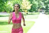 Young woman with headphones running in park — Stock Photo
