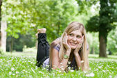 Young beautiful woman lying outdoors — Stock Photo